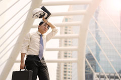Tired or stressful businessman stop walking in city after working. Tired or stressful businessman stop walking in the city after working with a building royalty free stock photos