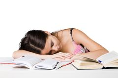 Tired Student. A tired student sleeping on her desk after studying hard, on white studio background Stock Images