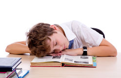 Tired student. Asleep while doing homework isolated on white background Royalty Free Stock Images