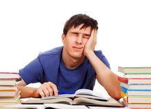 Tired Student with a Books. Tired Student at the Writing Table on the White Background Royalty Free Stock Image