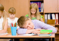 Tired student boy sleeping in classroom Stock Images