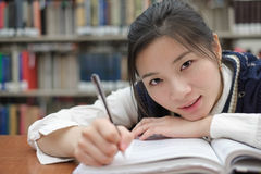 Tired student doing homework in library Stock Photography