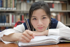 Tired student doing homework in library Royalty Free Stock Image