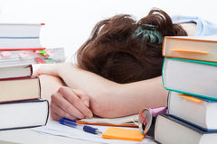 Tired student falling asleep during learning. Tired student falling asleep around heaps of books during learning stock photography