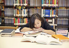 Tired student. Female student sleeping at the desk with piles of books Stock Image