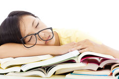 Tired student girl with glasses sleeping on the books Royalty Free Stock Photo