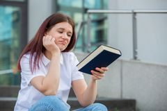 Tired student girl holding a book. Demotivated student sitting on campus stairs trying to study looking to camera. Student bored from learning to much tasks royalty free stock photos