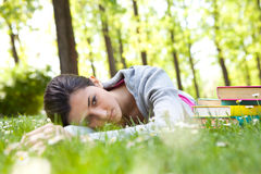Tired student girl lying on grass Royalty Free Stock Images