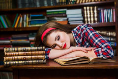 Tired student girl sleeping on the books in the library royalty free stock images