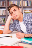 Tired student in library. Bored young man leaning his face on hand and looking at camera while sitting at the desk and in font of bookshelf Royalty Free Stock Photography