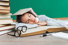 Tired student lies and sleep on the books. Photo of young girl in school. Back to school royalty free stock photo