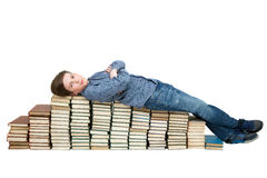 A tired student lying on a stack of books Royalty Free Stock Image