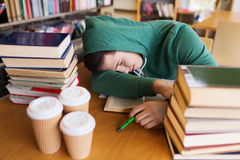 Tired student or man with books in library. People, education, session, exams and school concept - tired student or young man with books and coffee sleeping in Stock Images