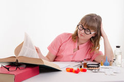 Tired student pharmacist flipping book Stock Photos