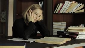 Tired student preparation of course work in a library in college, preparing for exams stock footage