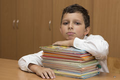 Tired student. Student is resting on stack of books royalty free stock photo