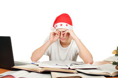 Tired student in santa's hat Stock Photo