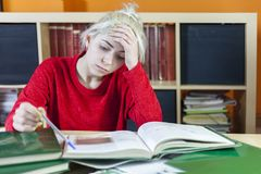 Tired student sitting with many books, with her head in hand. royalty free stock photos