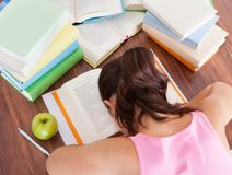 Tired student sleeping on book Stock Images