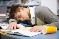 Tired student sleeping at the desk. In a library Stock Photos