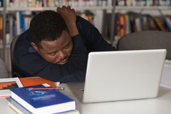 Tired Student Sleeping In Library. Sleeping African Student Sitting And Leaning On Pile Of Books In College - Shallow Depth Of Field Stock Photos