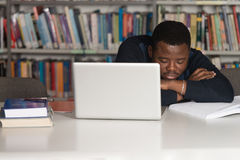 Tired Student Sleeping In Library. Sleeping African Student Sitting And Leaning On Pile Of Books In College - Shallow Depth Of Field Stock Images