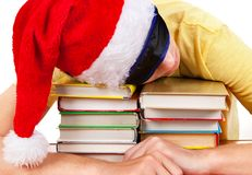 Tired Student sleeping. Student in Santa Hat sleep on the Books on a Table Royalty Free Stock Images