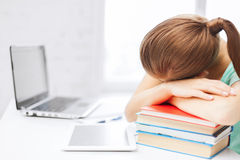 Tired student sleeping on stock of books Royalty Free Stock Image