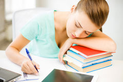 Tired student sleeping on stock of books Stock Image