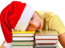 Tired Student sleeping. Student in Santa Hat sleep on the Books on a Table Stock Images