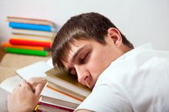 Tired Student sleeping. Tired Young Man sleep on the Books in the Room Stock Images