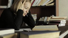 Tired student studying in the library in college. Female student sitting at the desk and grabs her head stock video footage