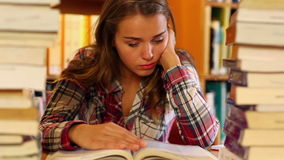 Tired student studying in the library surrounded by books stock video