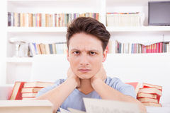 Tired student surrounded by books. Tired and exhausted student surrounded by books Royalty Free Stock Photo