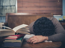 Tired student surrounded by books stock photography