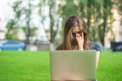 Tired student woman is holding and massaging her eyes or nose bridge while working outside royalty free stock photography