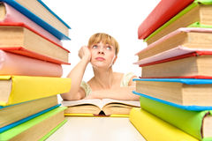 Tired student woman sitting at the desk surrounded with piles of. Books . Isolated Stock Images