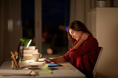 Tired student or woman touching neck at night home. Education, freelance, overwork and people concept - tired woman or student girl with tablet pc computer Royalty Free Stock Photography