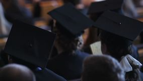 Tired students graduating from university campus, people sitting at hall. Stock footage stock video