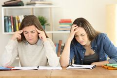 Tired students studying hard at home. Tired students studying hard memorizing notes preparing exam at home royalty free stock photo