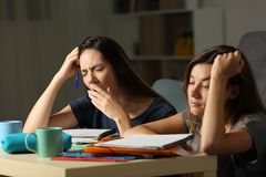 Tired students studying in the night at home stock images