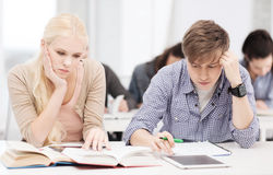 Tired students with tablet pc, notebooks and books. Education, technology and internet concept - tired students with tablet pc, books and notebooks preparing for royalty free stock photo