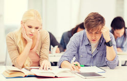 Tired students with tablet pc, notebooks and books. Education, technology and internet concept - tired students with tablet pc, books and notebooks preparing for royalty free stock photography