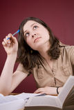 Tired of Studying. Pretty, young woman dreaming instead of studying in a home environment Stock Photography