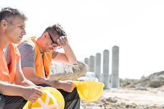 Tired supervisor sitting with colleague at construction site Royalty Free Stock Images