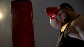 Tired sweaty boxer punching bag in gloves, sport lifestyle, health care, diet stock photos