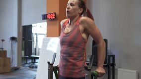 Tired sweaty fitness woman doing bar dips workout in gym stock video footage