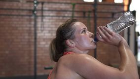 Tired sweaty fitness woman drinks water from a bottle during workout in gym stock video