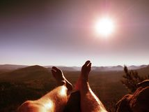 Tired  sweaty legs on peak of rock at broken pine tree. Hot windless summer day Stock Image