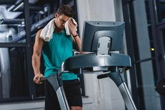 Tired sweaty sportsman with towel training on treadmill. In gym Stock Photography